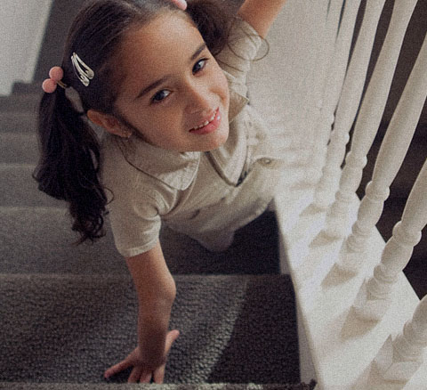 A young girl in pigtails climbing a staircase