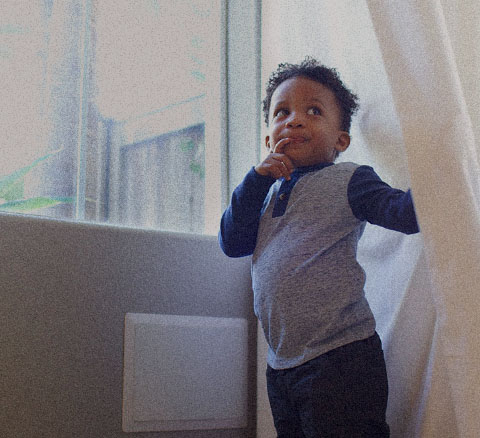 A young boy standing near a window against a curtain