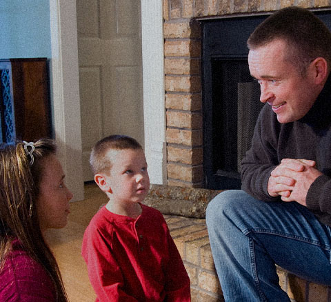 A father talks to his children near a fireplace
