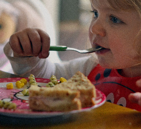 A young girl eats a spoonful of food.