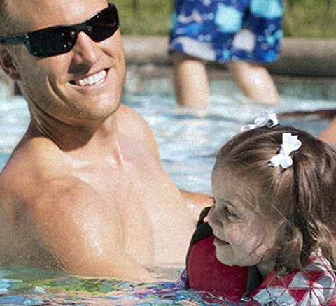 A girl swims with her dad