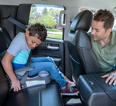 A boy and girl are strapped into their booster seats in a car