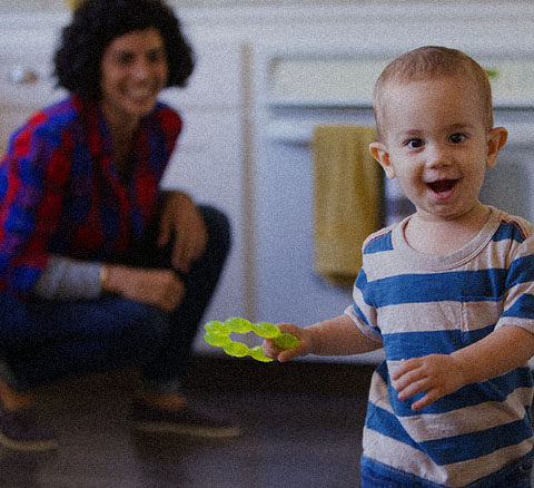 A toddler smiles in front of his Mom