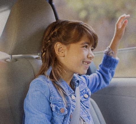 A girl waves from an open car window