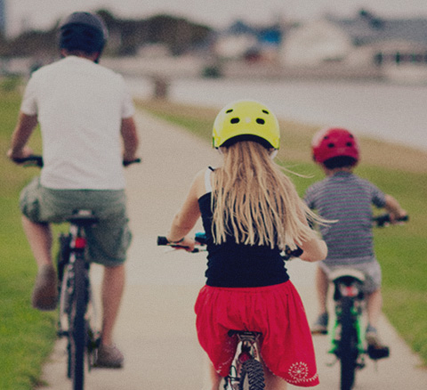 Father tightens the straps to his daughters bike helmet