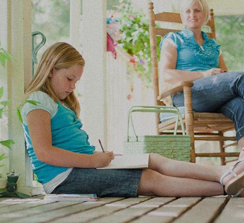 Child sitting on deck doing homework